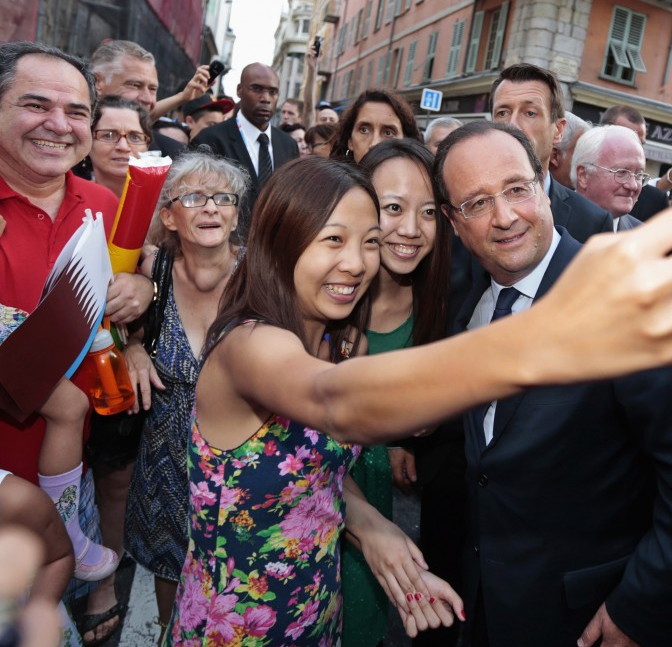 Chinese tourists snap a selfie with France's president in Paris.