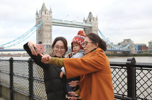 Three Chinese tourists pose for a selfie next to the River Thames in London